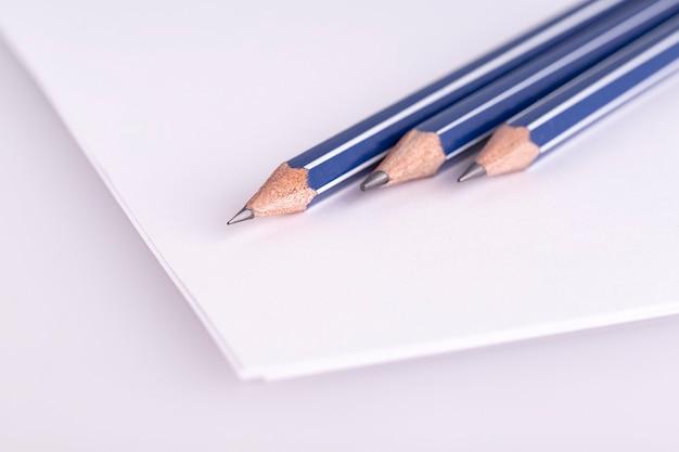 Три карандаша на белой бумаге