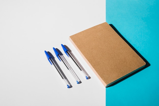 Three pens and closed book on dual white and blue backdrop