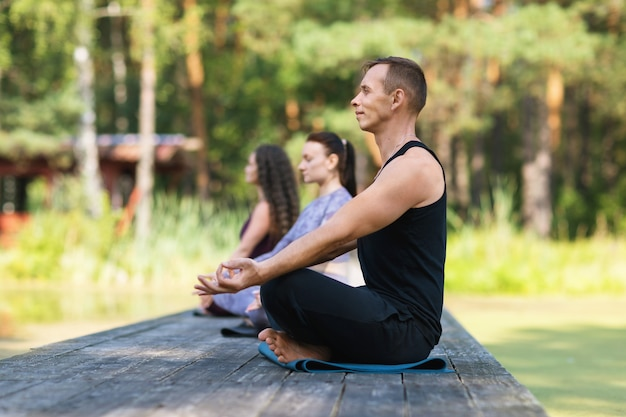 Three people are engaged in meditation sitting on a mat in the lotus position in the park