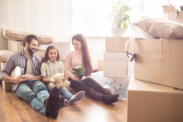 Three people are sitting together on the floor. they are surrounded with boxes full of stuff. father is holding big clock in hands, mother is holding a beautiful plant.
