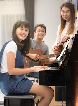 Three people asian family mother son and daughter playing music together
