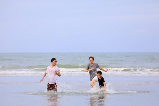 푸른 하늘을 배경으로 열대 해변에서 함께 뛰는 3명의 아시아 가족