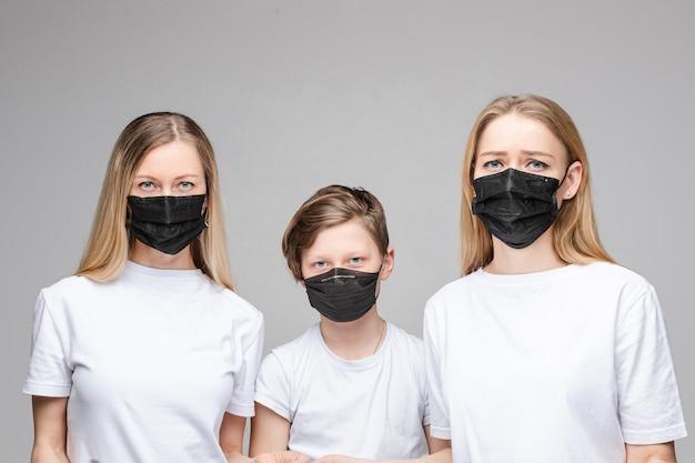 Three people in black anti-bacterial masks.