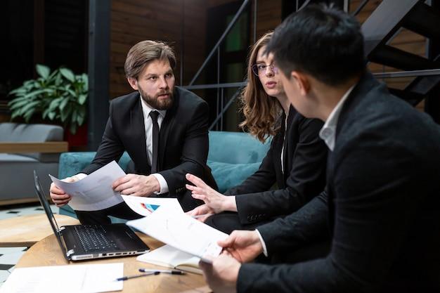 3人のビジネスマンがビジネスミーティングを開催し、作業プロジェクトについて話し合い、ビジネスマンは行われた作業に満足しています