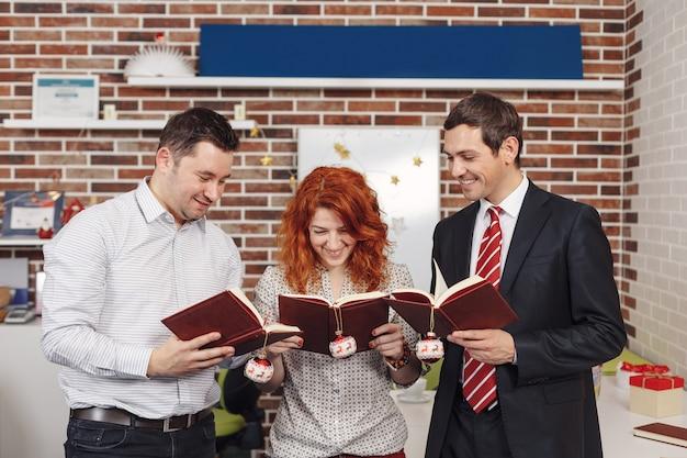 Три человека держат в руках книги