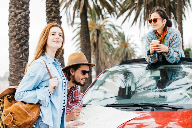Three people standing near car with road map