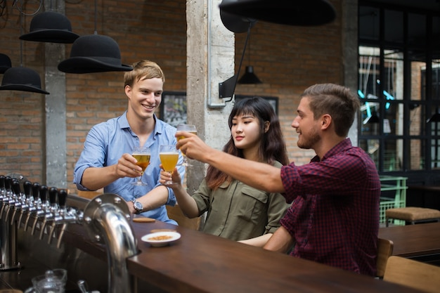 Three people toasting and drinking beer in pub