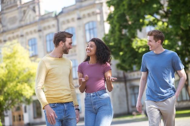 Три человека гуляют по парку и что-то обсуждают