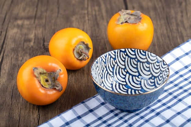 Three persimmon fruits and blue bowl on wooden background.