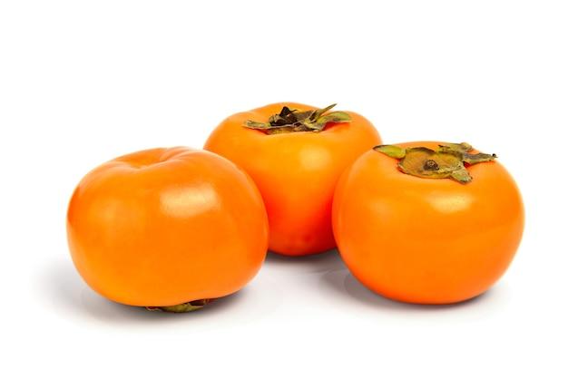 白い背景の上の3つの柿