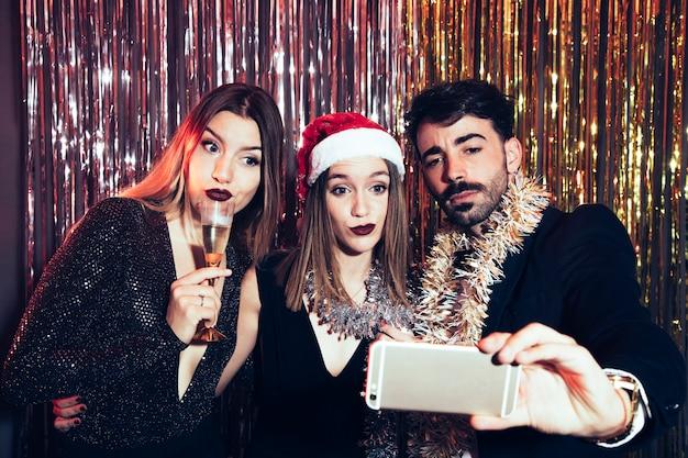 Tre persone che prendono selfie su partiti di nuovi anni