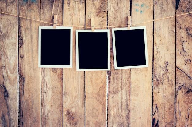 Три фото рамка висит на веревках и веревку с деревянным фоном.
