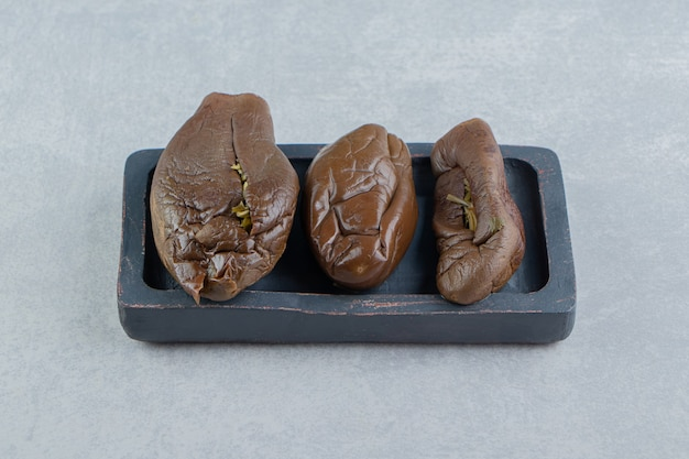 Three pickled eggplant on the board, on the marble surface