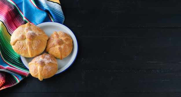 Three pieces of bread on black background. copy space. day of the dead. mexican holiday.
