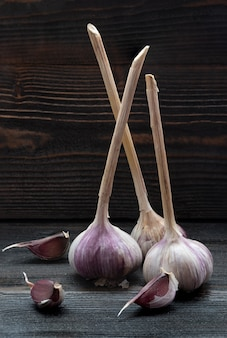 Three pieces of garlic on dark wooden desk surface