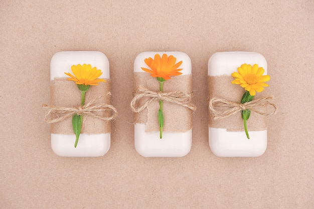 Three pieces of handmade natural soap set decorated with craft paper, scourge and orange calendula flowers. organic cosmetics,