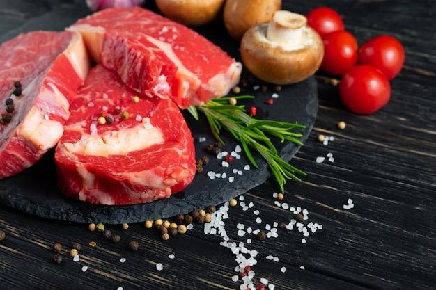 黒い木製のテーブルの上の石のまな板の上のジューシーな生の牛肉の3枚