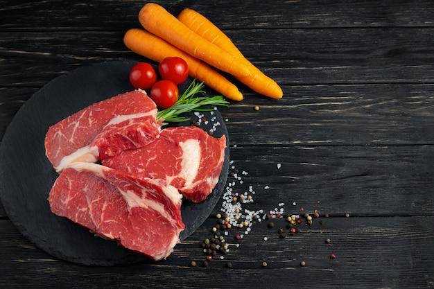 黒い木製のテーブル背景に石のまな板に野菜とジューシーな生の牛肉の3つの小品。