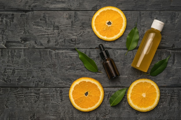 Три кусочка апельсина, бутылка с пипеткой и бутылка сока на деревянном столе.