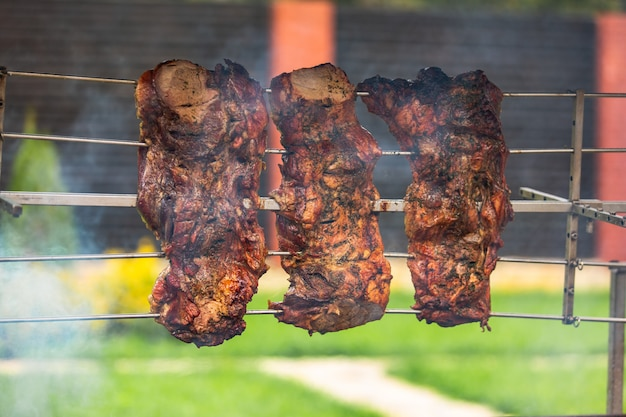 Three pieces of pork shish kebab are seasoned with spices and cooked on a skewer above the fire near the house in warm weather