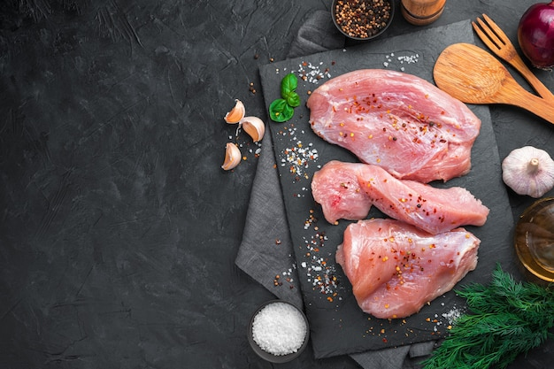 Three pieces of turkey fillet on a slate board with spices and garlic on a black background. top view with copy space.