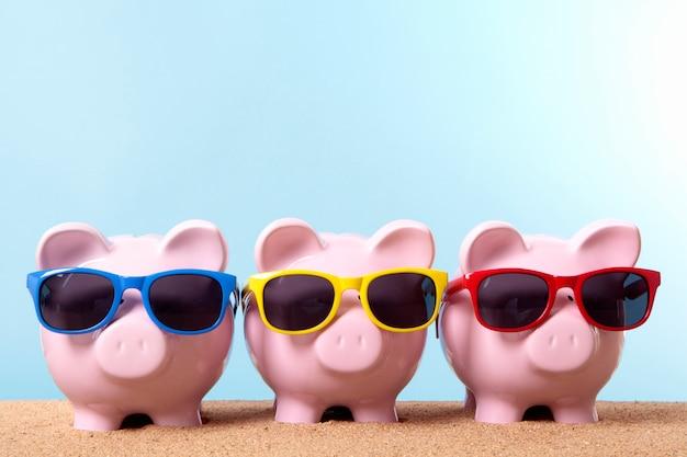Three piggy banks on a beach