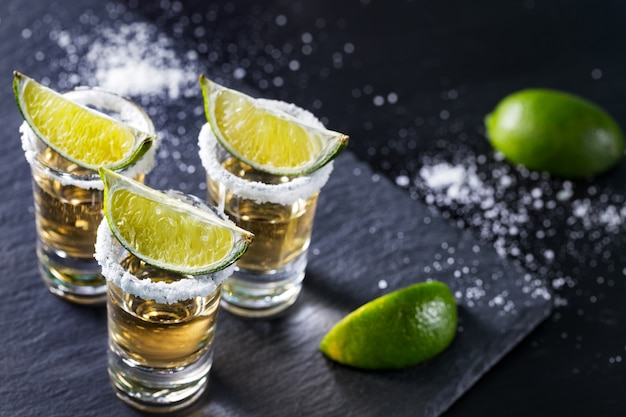Three piles of tequila with lime and salt