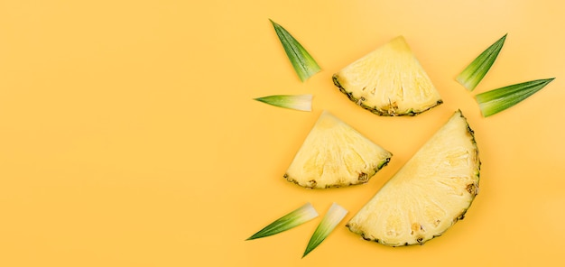 Три ломтика ананаса и листья на желтом фоне. летний фон