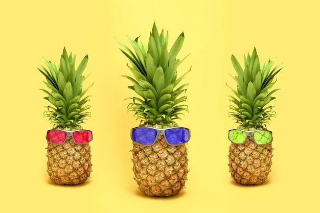 Три ананаса с очками на желтом фоне