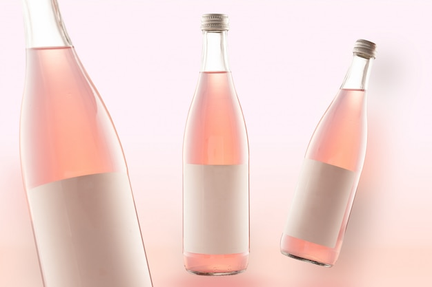 Three pink bottles of mockup-cola drinks, wine or beer. empty white labels