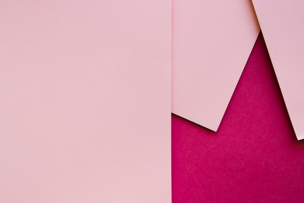 Tre carte di cartone rosa sulla superficie color magenta