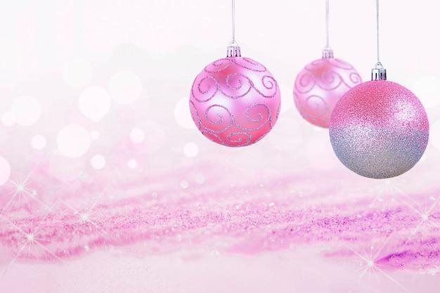 光沢のある焦点ぼけの背景に3つのピンクのクリスマスの装飾