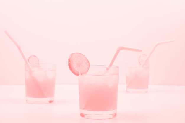 Three pink cocktail glasses on colored background