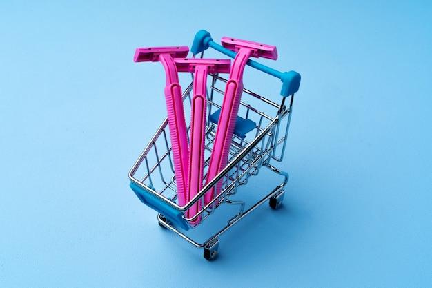 青い背景のショッピングカートに3つのピンクの使い捨てシェーバー