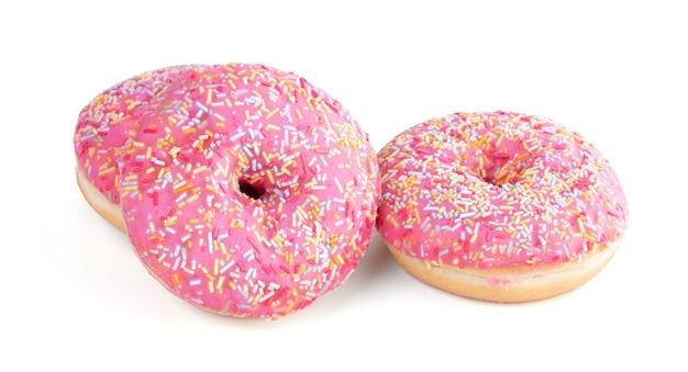 白地に小さなキャンディーと3つのピンクのドーナツ