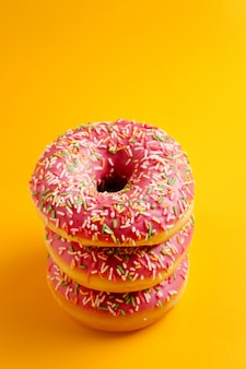 Three pink donuts on yellow  top view copy space