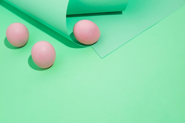 Three pink easter eggs with rolled paper