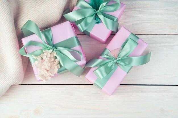 리본과 흰색 나무 바탕에 스웨터와 3 개의 분홍색 선물 상자.