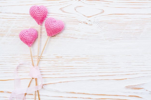 Three pink knitted hearts with pink ribbon on a white wooden background