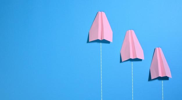 파란색 표면에 3 개의 분홍색 종이 비행기. 독창성과 성공의 개념. 비즈니스에서 승리와 경쟁, 복사 공간