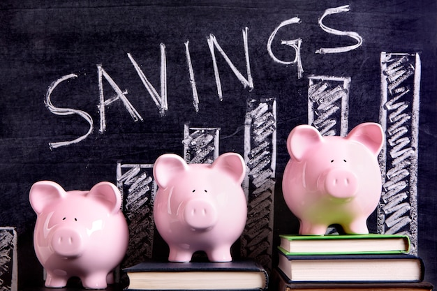 Three pink piggy banks standing on books next to a blackboard with savings chart.