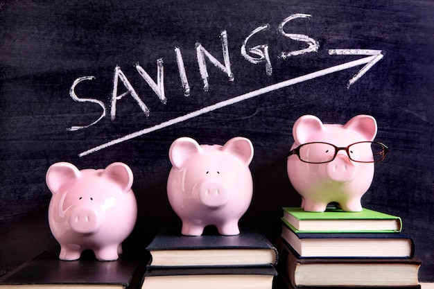 Three pink piggy banks standing on books next to a blackboard with simple savings message.