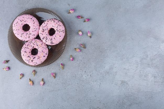 Три розовых сладких пончика с распускающимися розами на стеклянной тарелке.