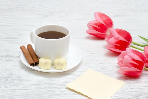 Three pink tulips, mug of coffee and cinamon