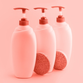 Three plastic bottles with dispenser on coral background.