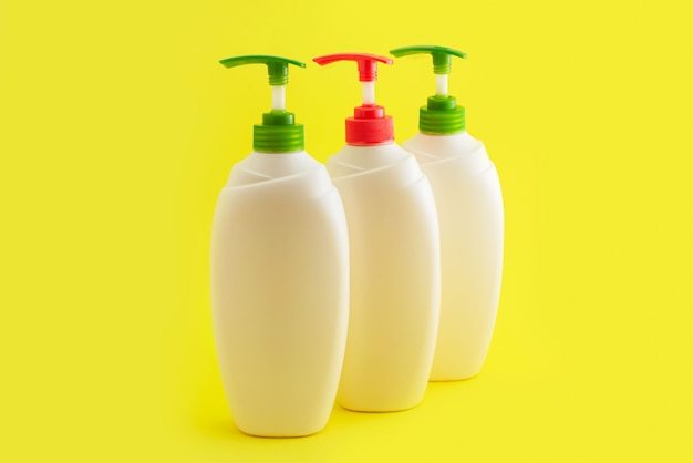 Three plastic bottles with dispenser on yellow background.