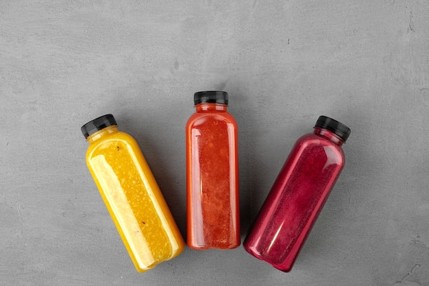Three plastic bottles with freshly squeezed juice on gray table