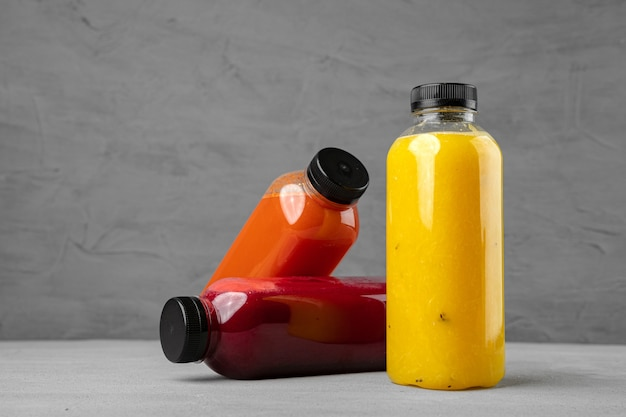 Three plastic bottles with freshly squeezed juice on gray