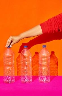 Три пластиковые бутылки, одна рука держит одну из них. переработка, концепция окружающей среды