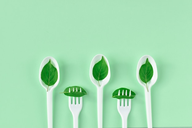 Three plastic spoons and two forks with leaves from the bottom